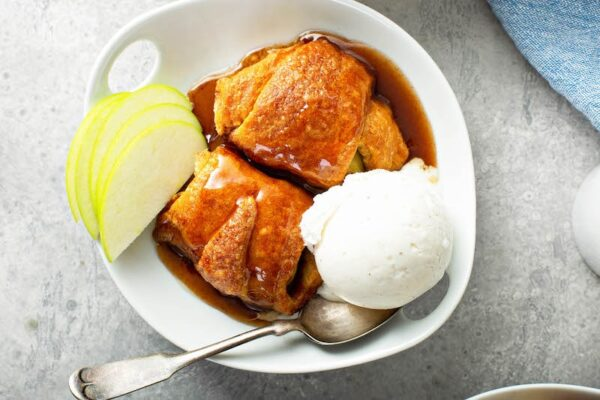 Two dumplings in a bowl with vanilla ice cream and apple slices.