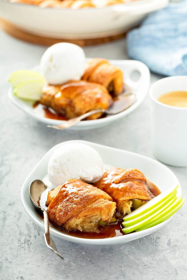 Apple Dumplings in bowls with ice cream and apple slices.