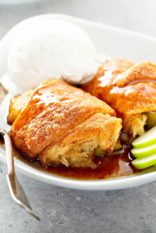 Two large apple dumplings with sauce in a bowl.
