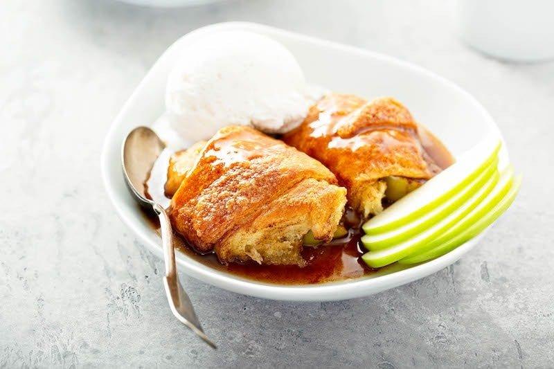Two large apple dumplings with cinnamon sugar sauce in a bowl.