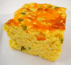 Side view of yellow cornbread topped with melted cheddar cheese on a white plate