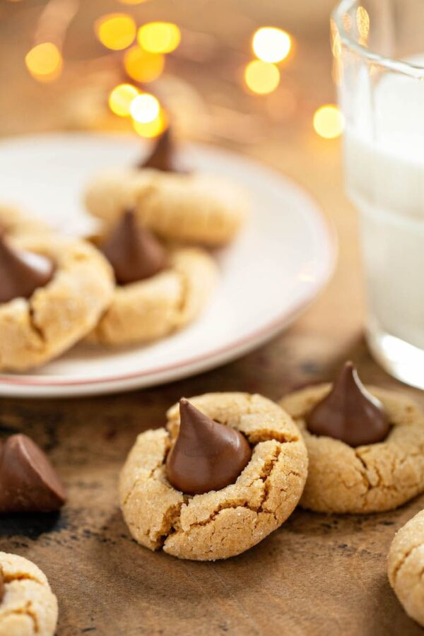 Peanut Butter Blossoms on a plate and with a glass of milk.