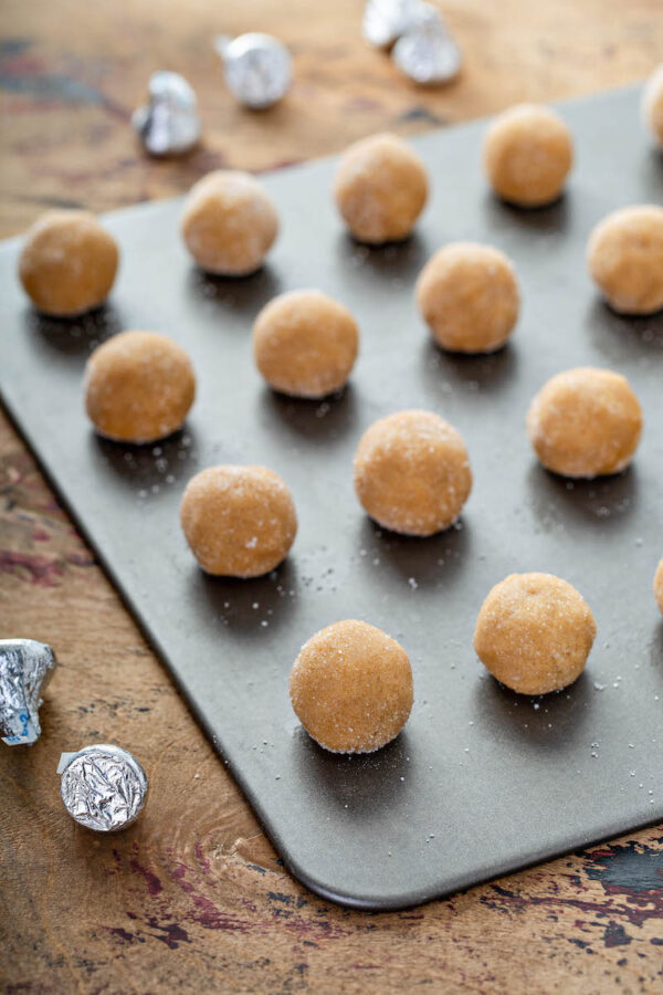 Peanut Butter Blossoms dough rolled into balls and sugar and then placed on a baking sheet.