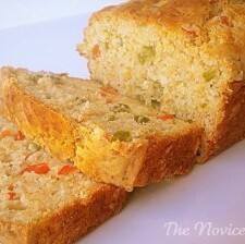 golden yellow bread loaf with two slices cut off on a white plate. Inside of bread showing red and green jalapeno pepper pieces.