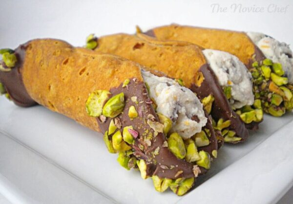 Close up view of three cannoli shells stuffed with white ricotta cheese, shell ends dipped in chocolate and encrusted with green pistachios on a white plate