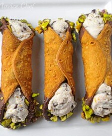 Three cannoli on a white plate with chocolate and pistachio on the ends.