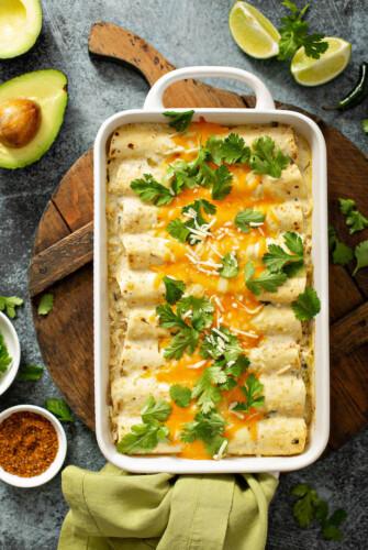 Baking dish with chicken enchiladas inside