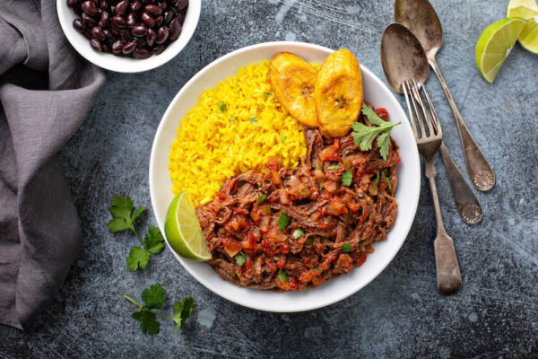 Ropa vieja in a white bowl with rice and plantains.