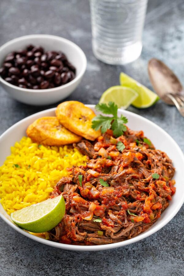 Ropa Vieja on a plate with rice, plantains and black beans.