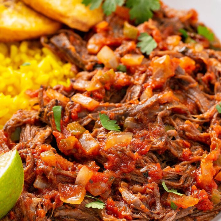 Ropa Vieja is a classic Cuban dish that is bursting with bold flavor! Flank steak is slow cooked all day and shredded in a rich and flavorful sauce with onions, peppers and garlic. #RopaVieja #RopaViejaRecipe #CubanRecipes #Cuban #SlowCookerRopaVieja #CrockpotRopaVieja #BeefRecipes #FlankSteakRecipes #CrockpotRecipes #SlowCookerRecipes
