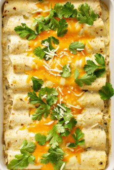 Sour cream chicken enchiladas with cheese and cilantro on top.