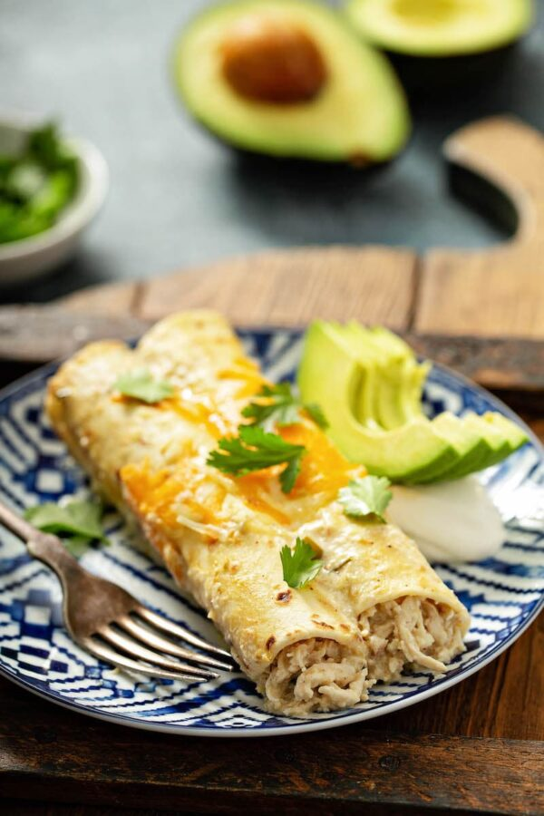 Sour cream chicken enchiladas on a plate with a fork.