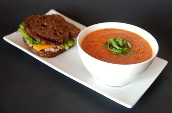 White rectangle plate topped with a sandwich alongside a white bowl filled with red tomato soup topped with a green basil garnish on a dark background