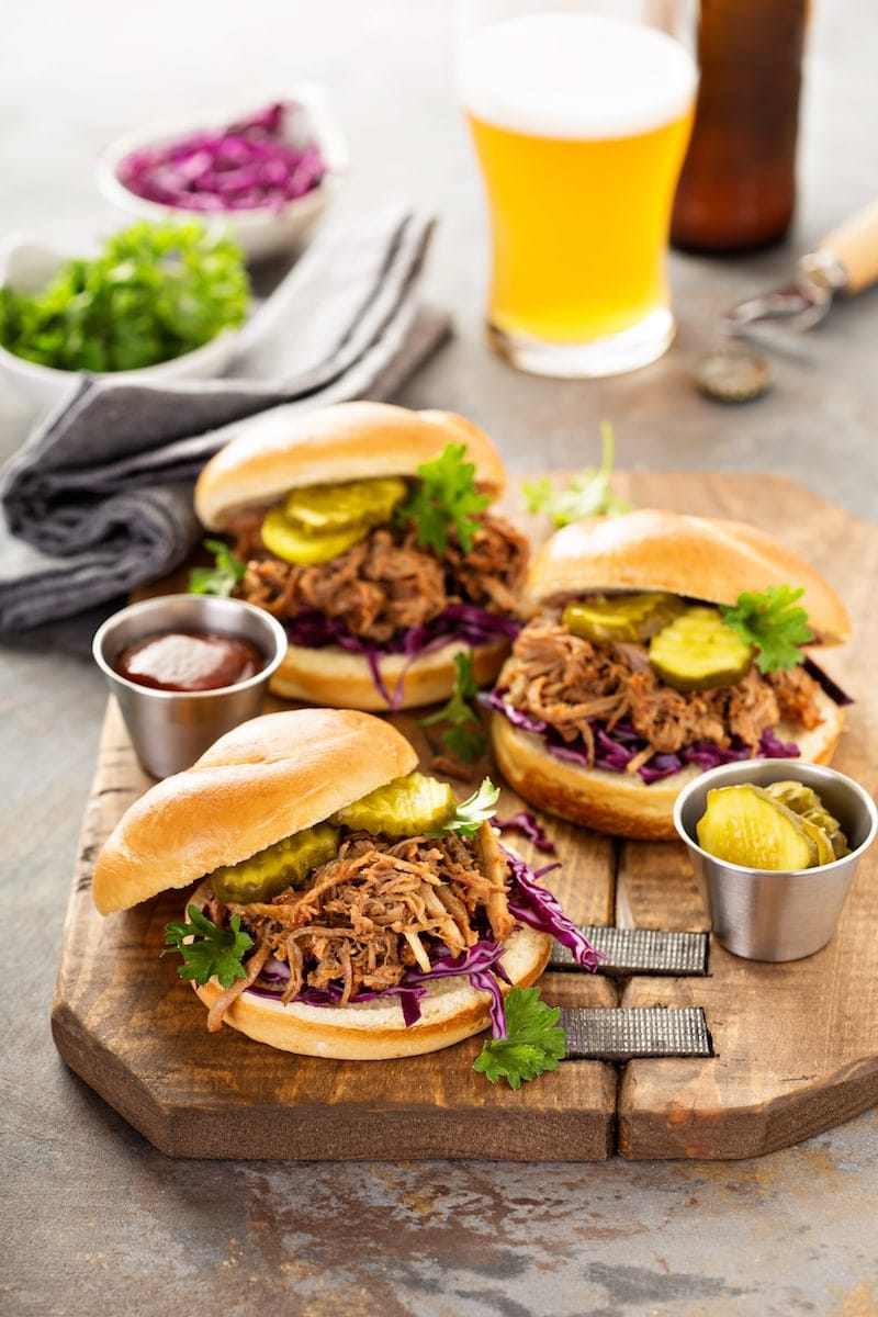 Pulled pork in buns with pickles on top.