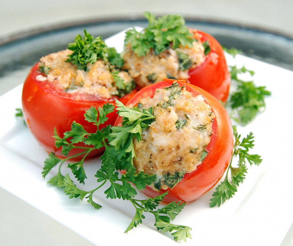 Three stuffed tomatoes on a plate with parsley on top.