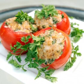 Close up view of three red tomatoes stuffed with cheese and breadcrumbs garnished with green parsley on a white plate