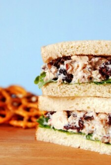 Side view of two half sandwiches filled with chicken salad, raisins and lettuce on a wood board with light blue background