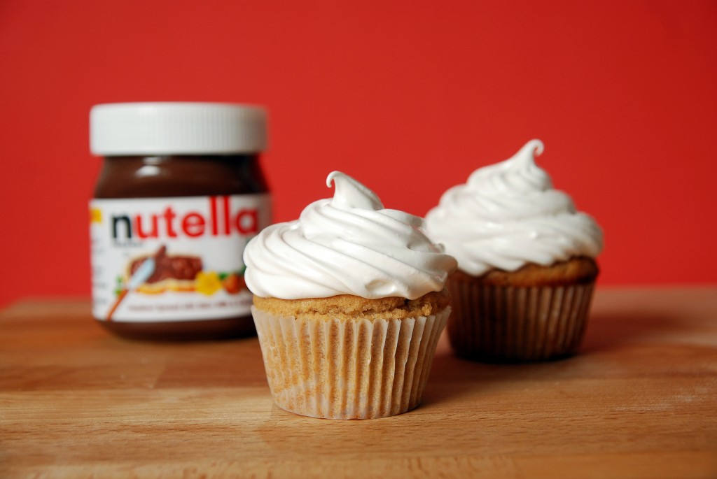 Two peanut butter cupcakes with marshmallow frosting and a jar of Nutella