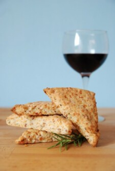 Four scones stacked on a wood board in front of a glass of red wine on a light blue background