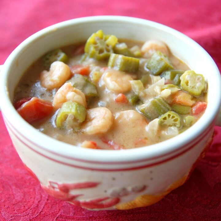 A white bowl with handles is filled with seafood gumbo