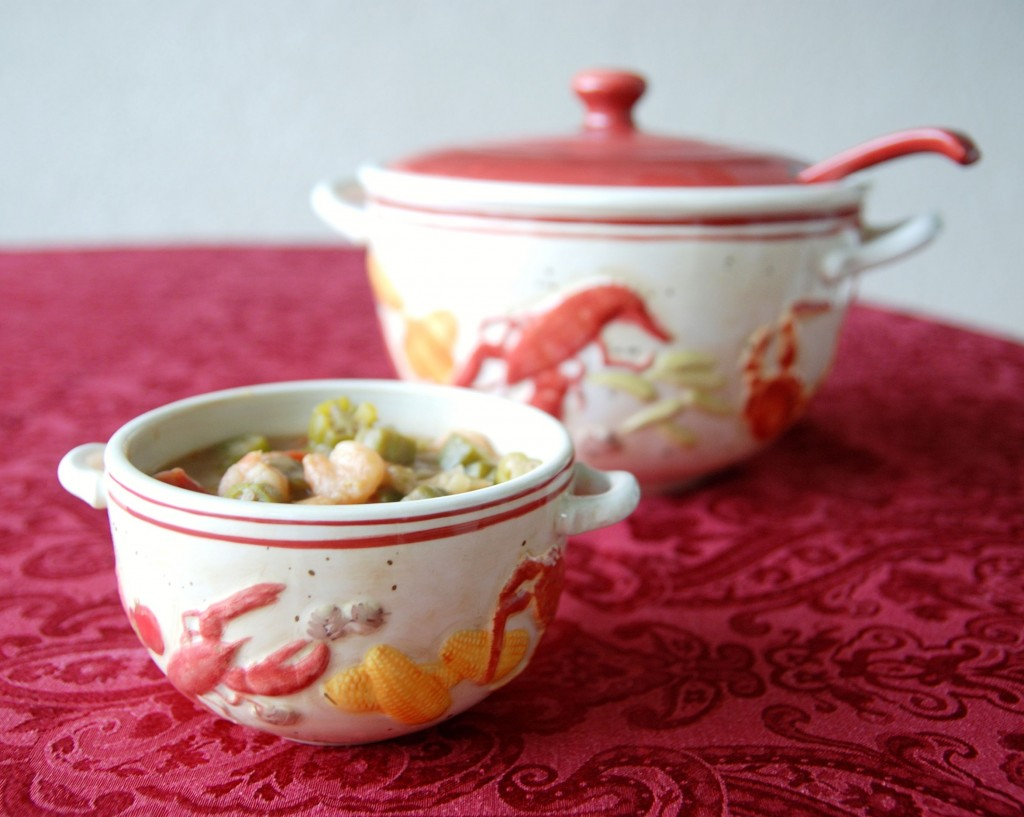 A decorative bowl with handles is filled with seafood gumbo