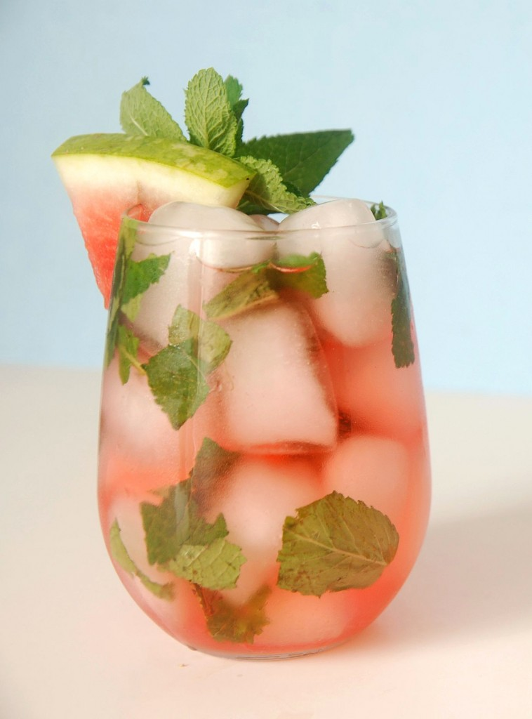 An ice and cocktail filled glass with fresh mint and a slice of watermelon inside