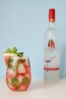 A glass filled with a watermelon cocktail, fresh mint and a watermelon slice