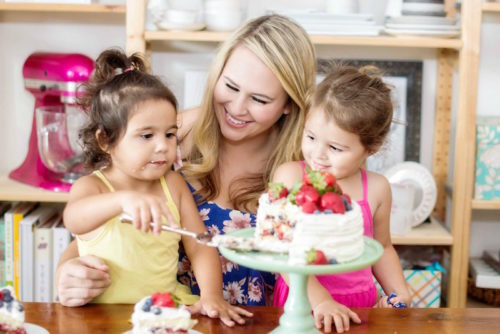Woman with two little girls in front of a cake