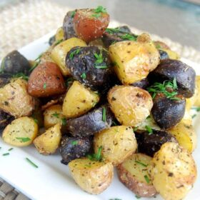 Roasted potatoes with fresh herbs on top stacked on a plate