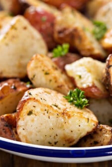 Close up image of roasted potatoes on a plate with herbs.