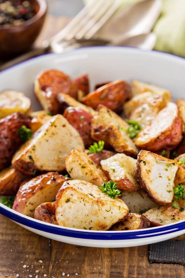 Up close image of oven roasted potatoes in a white bowl.