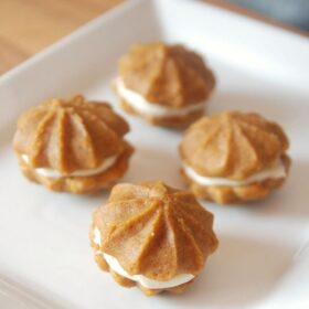 a white plate filled with four pumpkin whoopie pies