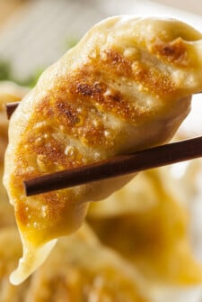 Chinese Dumpling (potsticker) being held with chopsticks.