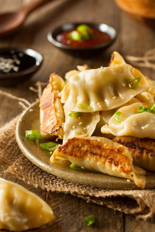 Potstickers on a plate with soy sauce, scallions and sesame seeds on top.