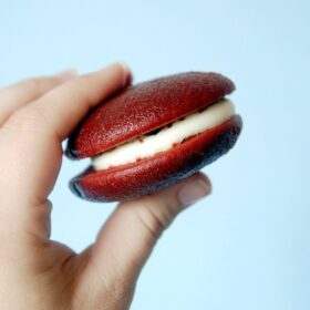 a hand holding a red velvet whoopie pie