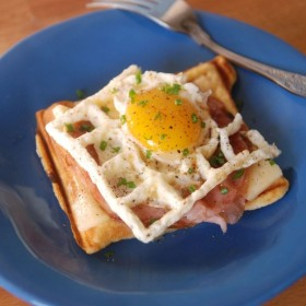 croque madame on a blue plate with a fork