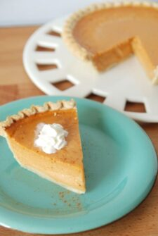A slice of Sweet Potato Buttermilk Pie topped with whipped cream on a teal plate
