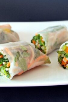 veggie spring rolls sliced in half on a white plate