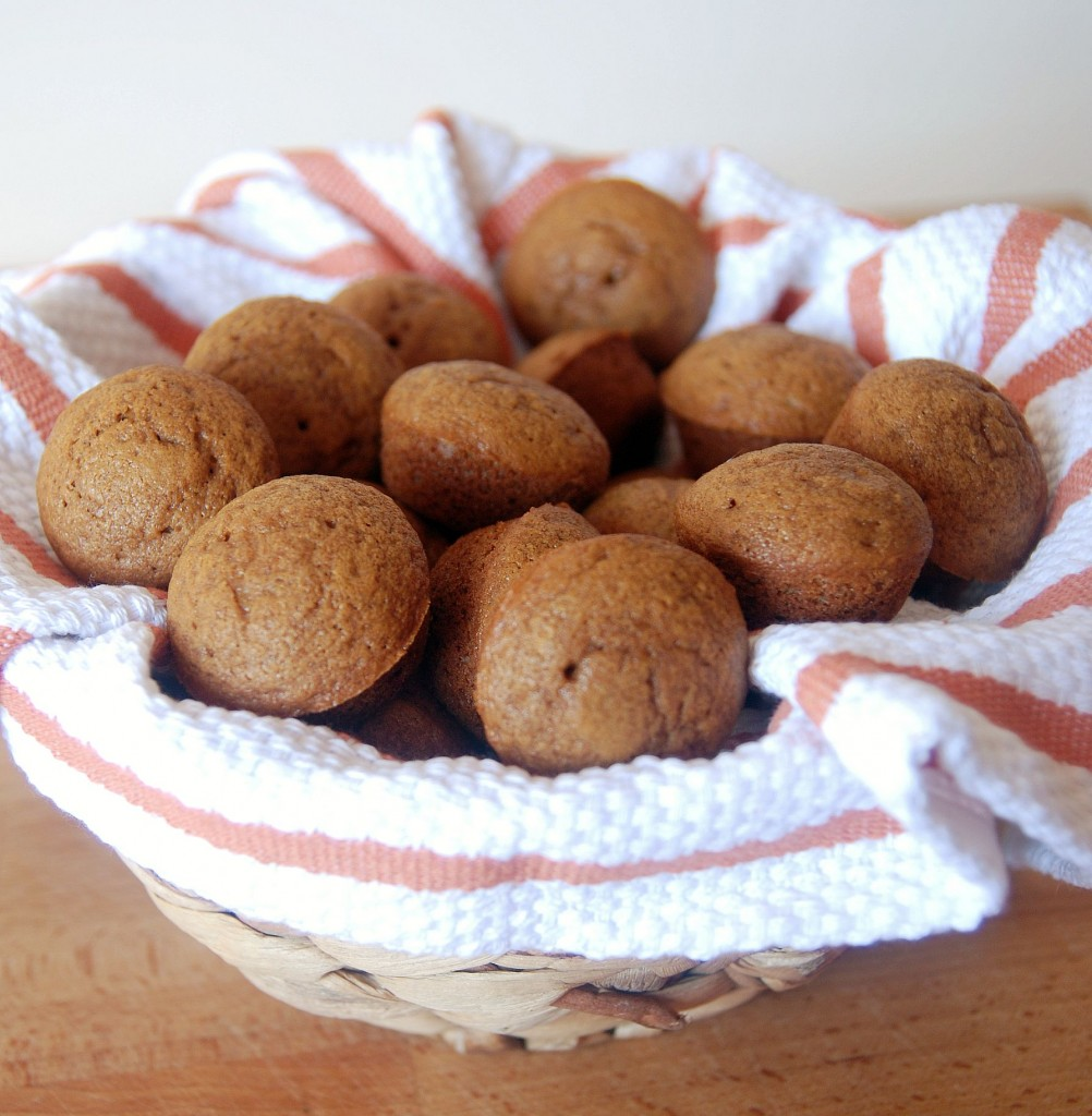 Basket filled with a tea towel and mini gingerbread muffins.