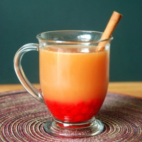 A glass mug filled with apple cider and red hots and a cinnamon stick