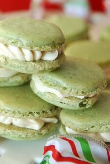 Green pistachio macarons stacked on top of each other with red and green ribbon