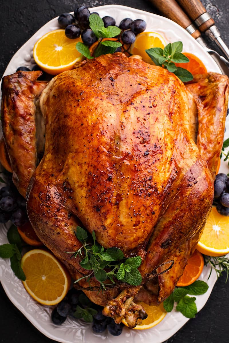 Golden brown roasted turkey on a white platter for how to cook a turkey.