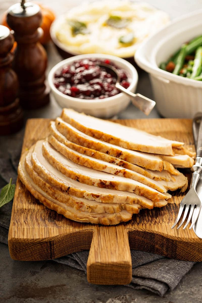Sliced roasted turkey breast on a chopping board for how to cook a turkey.
