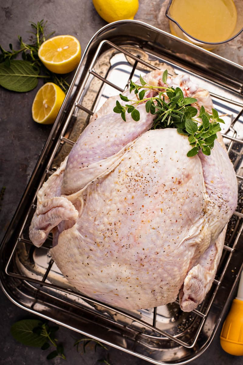 Raw turkey in a turkey roasting pan for how to cook a turkey.