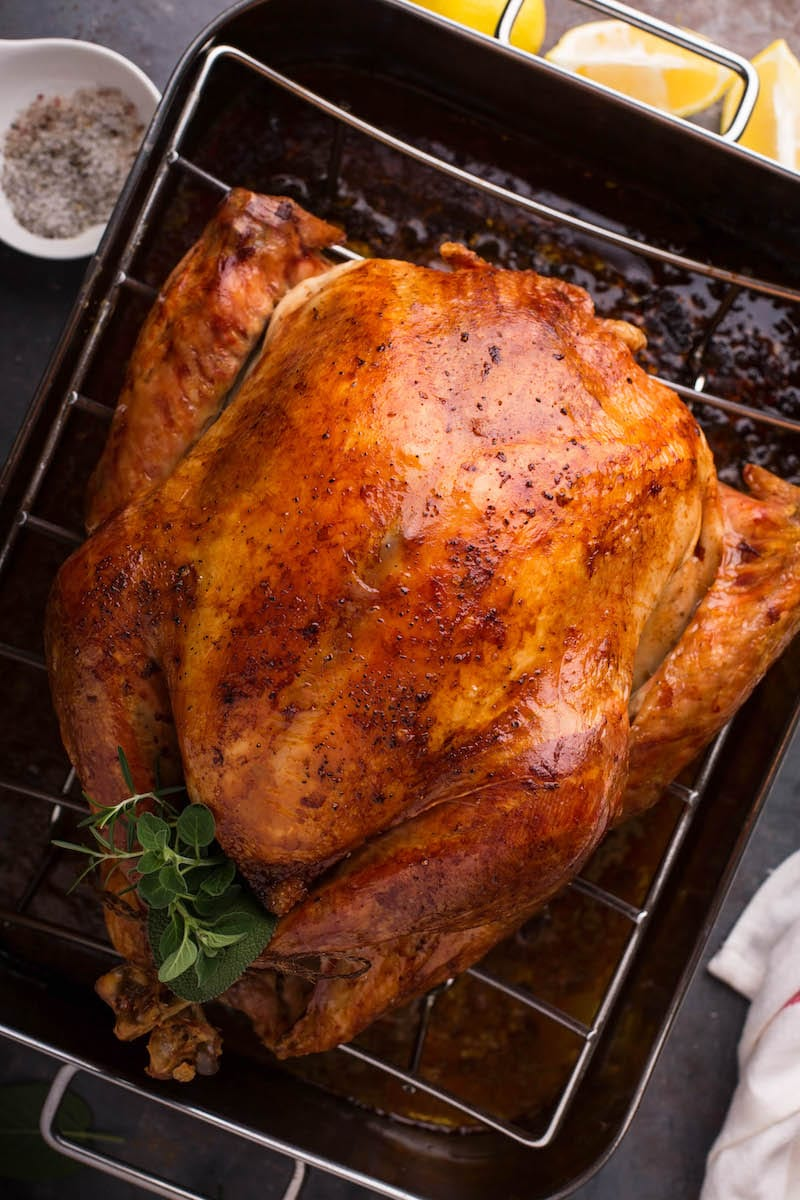 A cooked Thanksgiving turkey in a roasting rack.