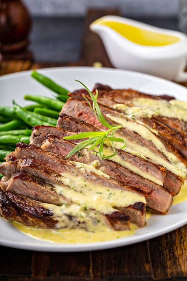 Bearnaise sauce spooned over a sliced steak.