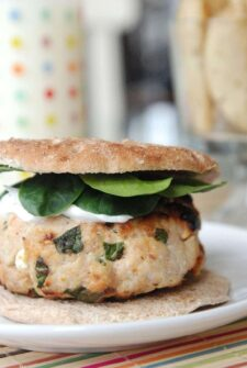 Greek Turkey Burger with spinach and tzatziki on a bun on a white plate.