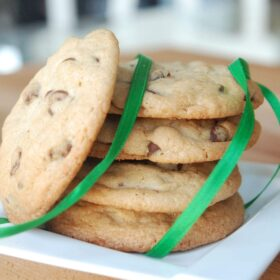 Chocolate chip cookies on a white plate with a green ribbon.