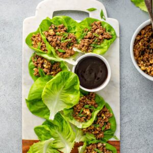 Lettuce wraps platted with dipping sauce.
