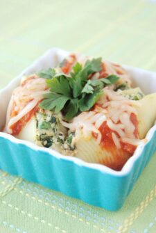 Stuffed shells in a small square serving dish with cheese on top